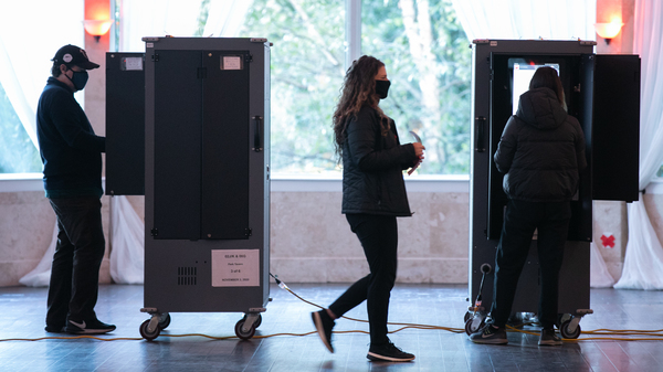 Voters in Atlanta casting their ballots on voting equipment made by Dominion Voting Systems. After losing the election, former President Trump and his allies spread conspiracy theories about the company, which has responded with defamation suits to combat the disinformation.